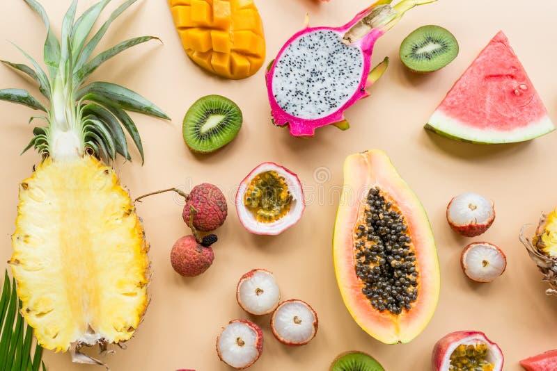 """Åšwieże egzotyczne owoce i tropikalne liÅ›cie dÅ'oni na pastelowo-pomaraÅ""""czowym tle - papaya, mango, ananasa, owoce mÄ™czennicy zdjęcia royalty free"""