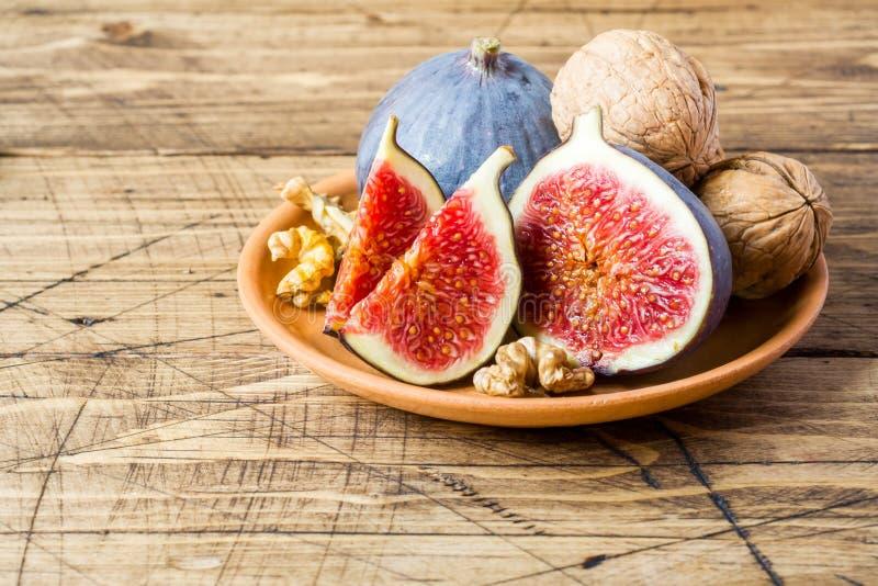 Świeże figi całe i rżnięci nasiona orzechy włoscy na talerzu stary w zdjęcie royalty free