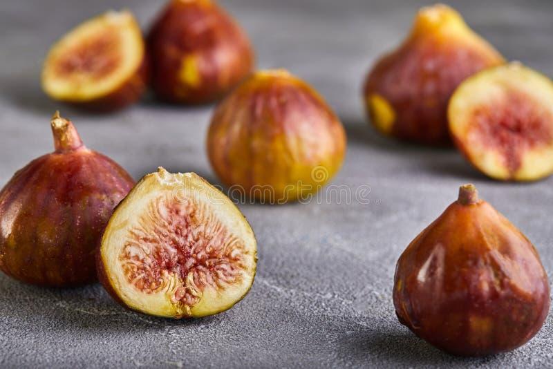 Świeże figi całe i rżnięte w kawałki na szarym tle pojęcie zdrowy fotografia stock