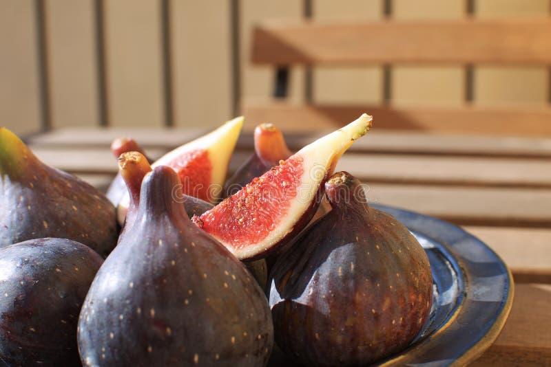 Świeże figi na ceramicznej czarnego talerza Sunligh Drewnianej stołowej kopii interliniują jesień zbiera F fotografia royalty free