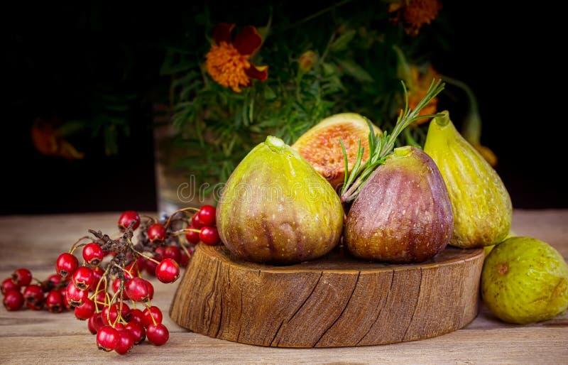 Świeże figi w drewnianym tle z czerwonymi jagodami zdjęcie royalty free