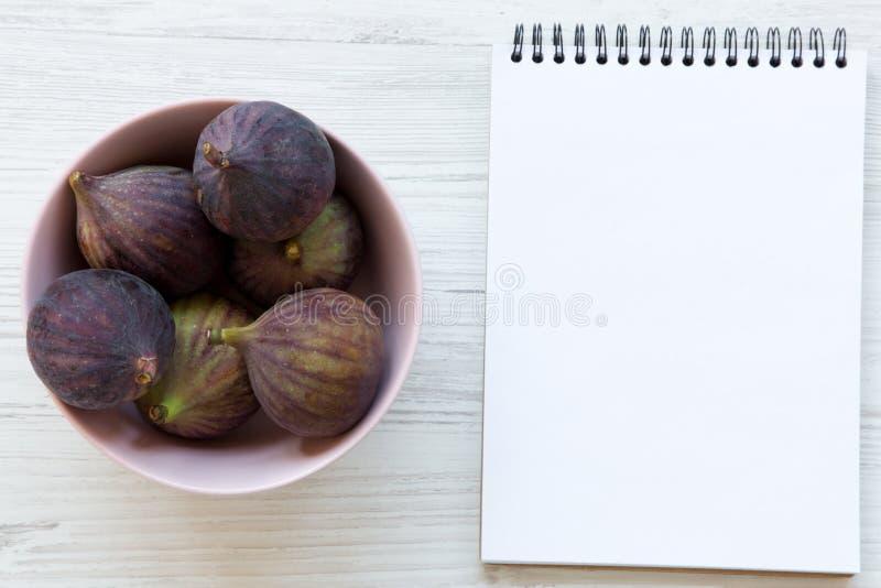 Świeże figi w różowym pustego miejsca notepad na białym drewnianym stole i pucharze Odgórny widok, koszt stały, od above obrazy royalty free