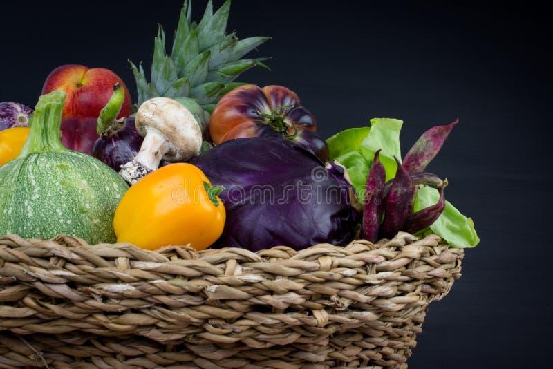 ŚWIEŻE I ORGANICZNIE owoc W TKANYM koszu ODIZOLOWYWAJĄCYM NA CZARNYM tle I warzywa obrazy stock