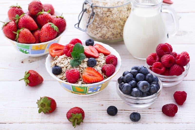 Świeże jagody truskawka, malinki i naturalni płatki dla śniadania, kobiety dolewania mleko w puchar z muesli wierzchołkiem obraz stock