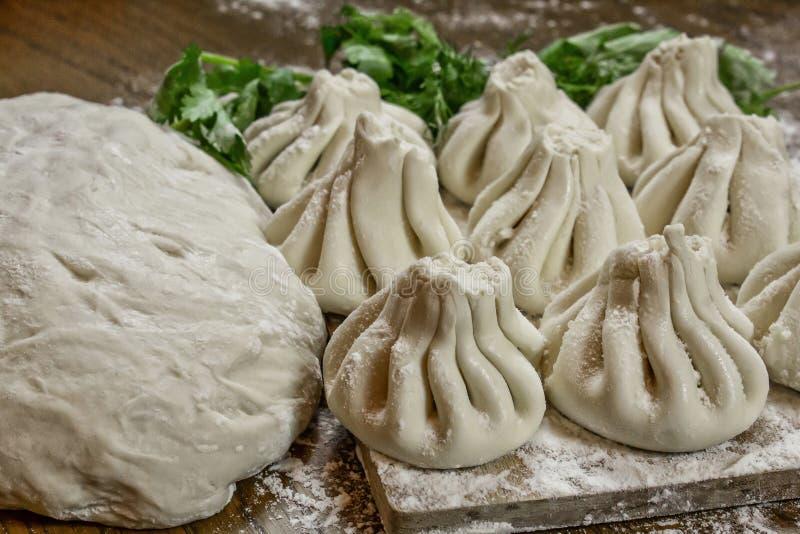 Świeże khinkali z ciasta z mięsem w środku, narodowa gruzińska danie Świeże ciasto, mąka i zioła fotografia stock