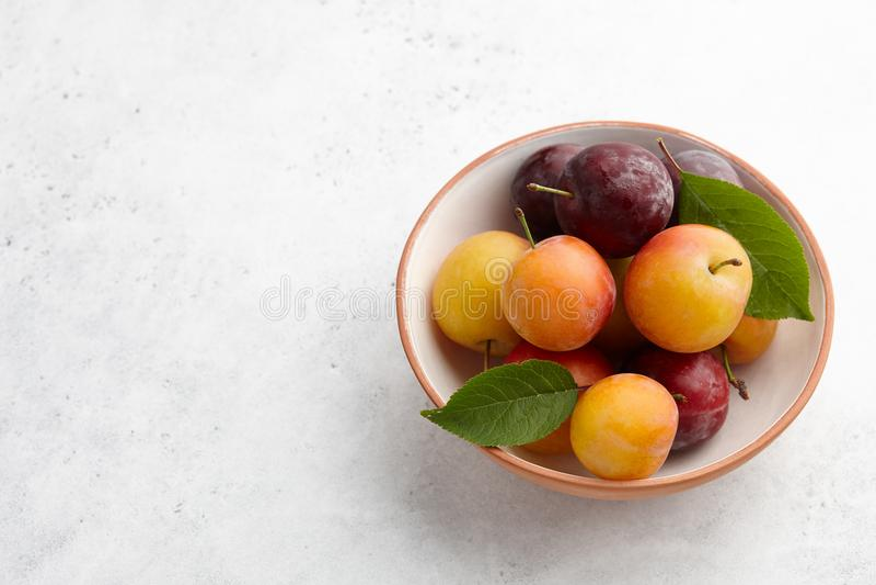 Świeże kolorowe śliwki w pucharze na bielu drylują tło zdjęcie stock
