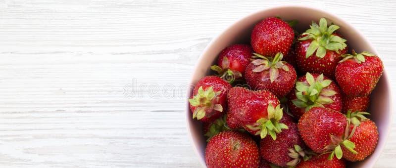 Świeże organicznie truskawki w różowym ceramicznym pucharze na białej drewnianej powierzchni, zasięrzutny widok Od above, mieszka obraz stock