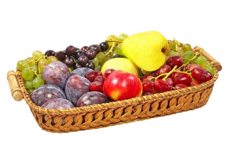 Świeże owoc na słomianym garnku. Odosobniony. obrazy royalty free