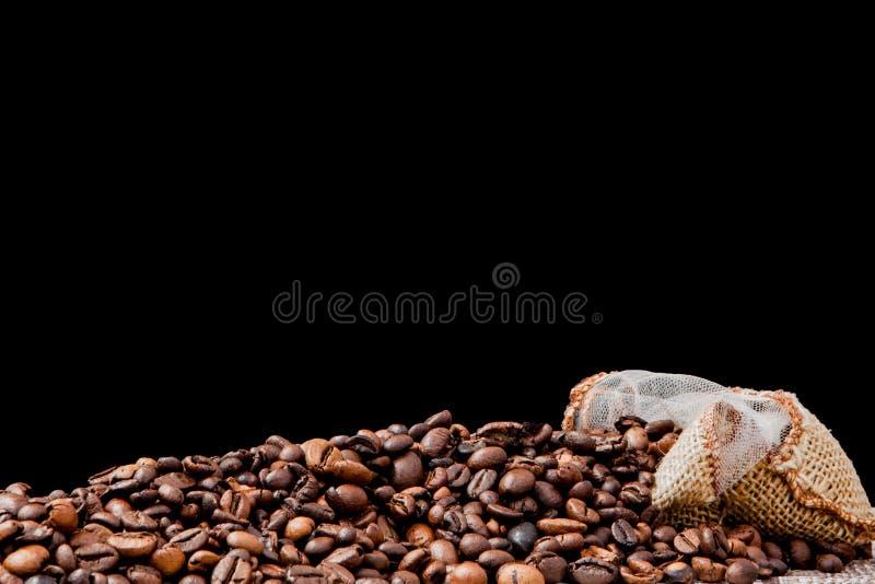 Świeże piec kawowe fasole spada za worku na czarnym tle Brown kawowe fasole rozpraszali od torby na stole zdjęcia stock