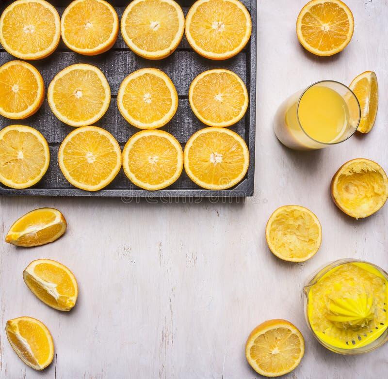 Świeże pokrojone pomarańcze w drewnianym pudełku z juicer i szkłem sok na drewnianym nieociosanym tło odgórnego widoku zakończeni zdjęcie stock