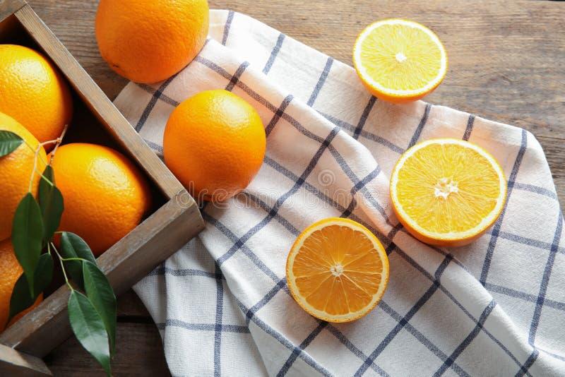 Świeże pomarańcze z liśćmi i wieśniak boksują na drewnianym stole obrazy stock