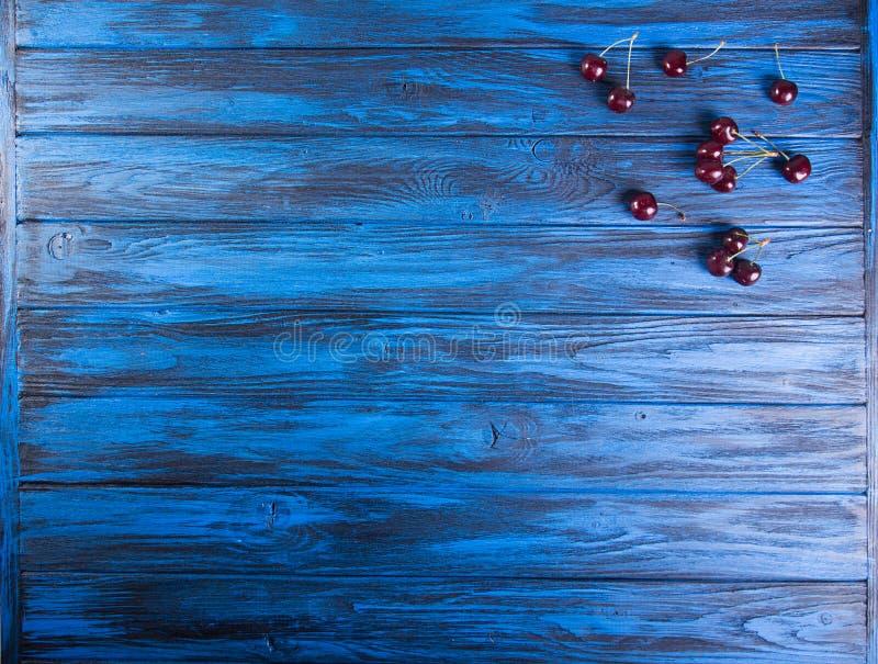 Świeże słodkich wiśni owoc na błękitnym drewnianym tle overhead fotografia stock