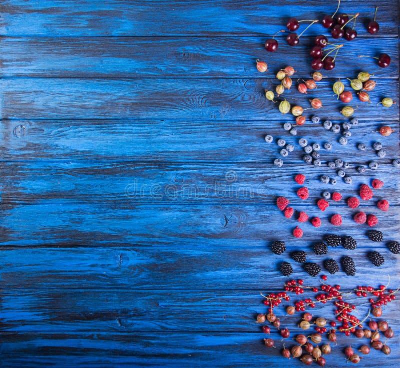 Świeże słodkich wiśni owoc na błękitnym drewnianym tle overhead zdjęcia stock