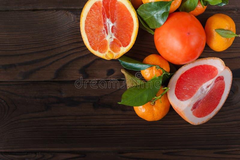 Świeże soczyste owocowe pomarańcze, tangerines, persimmon, grapefruitowy na białym talerzu w rżniętym zbliżeniu na zmroku texture zdjęcia royalty free