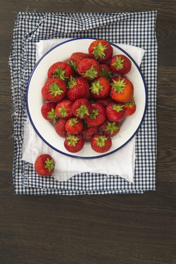 Świeże soczyste truskawki na rocznika enamelware crockery na rusti obraz royalty free