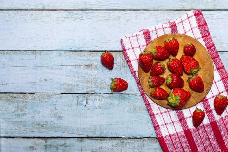 Świeże soczyste truskawki z liśćmi na błękitnym drewnianym tle zdjęcie royalty free