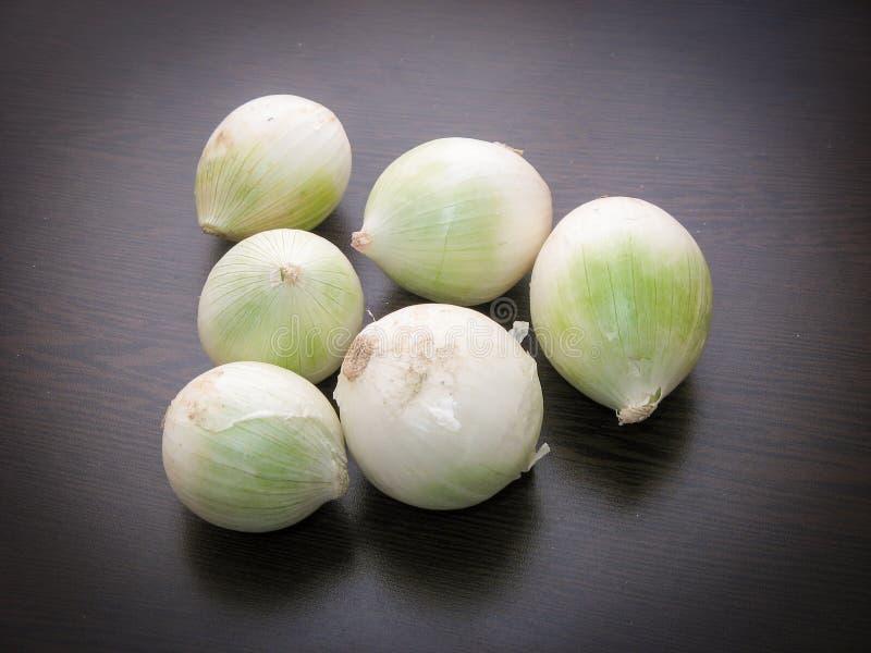 Świeże surowe białe cebule na drewnianym stole Zbliżenie suche cebulkowe żarówki na ciemnym tle zdjęcia royalty free