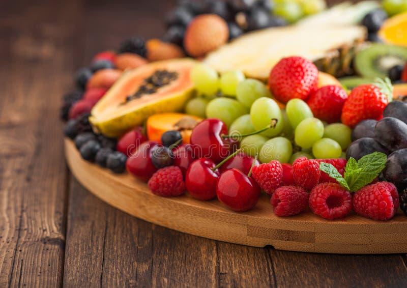 Świeże surowe organicznie lato jagody i egzotyczne owoc w round wielkiej tacy na drewnianym kuchennym tle Melonowiec, winogrona,  zdjęcie stock