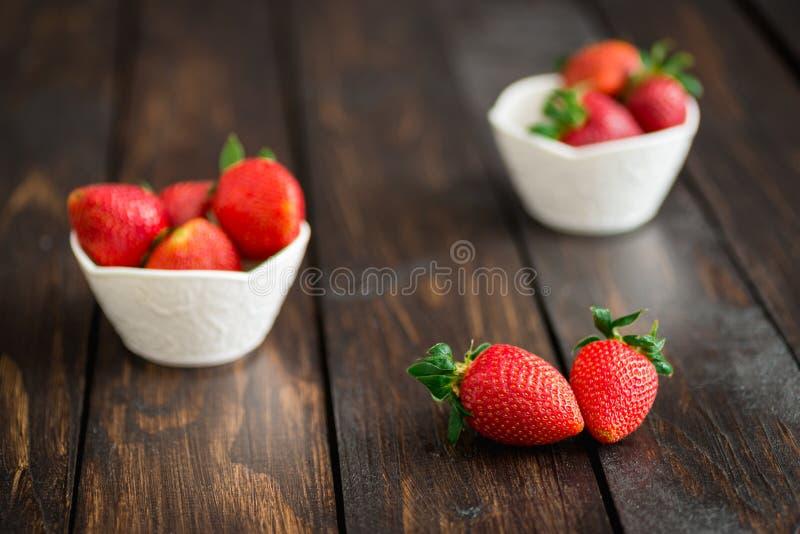Świeże truskawki w białym pucharze na starym drewnianym stole zdjęcie royalty free