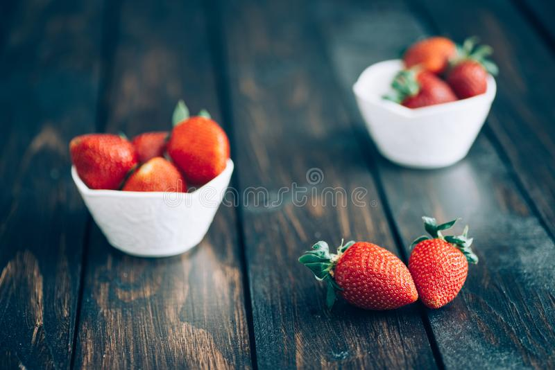Świeże truskawki w białym pucharze na starym drewnianym stole obraz stock