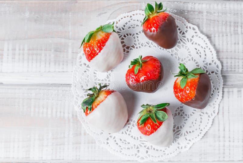 Świeże truskawki zamaczać w ciemnej i białej czekoladzie na lekkim tła zakończeniu up fotografia royalty free