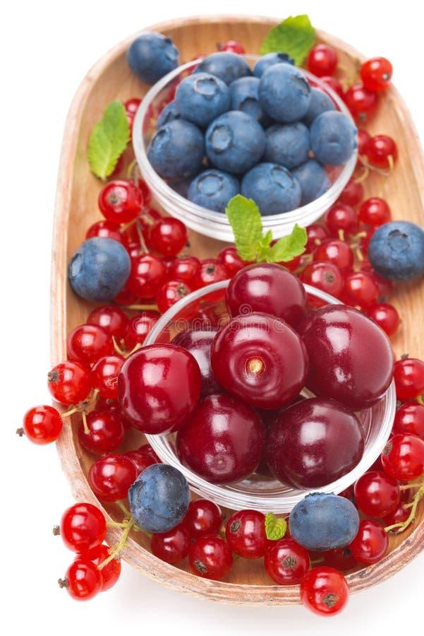 Świeże wiśnie, czarne jagody i czerwoni rodzynki w drewnianym pucharze, obraz royalty free