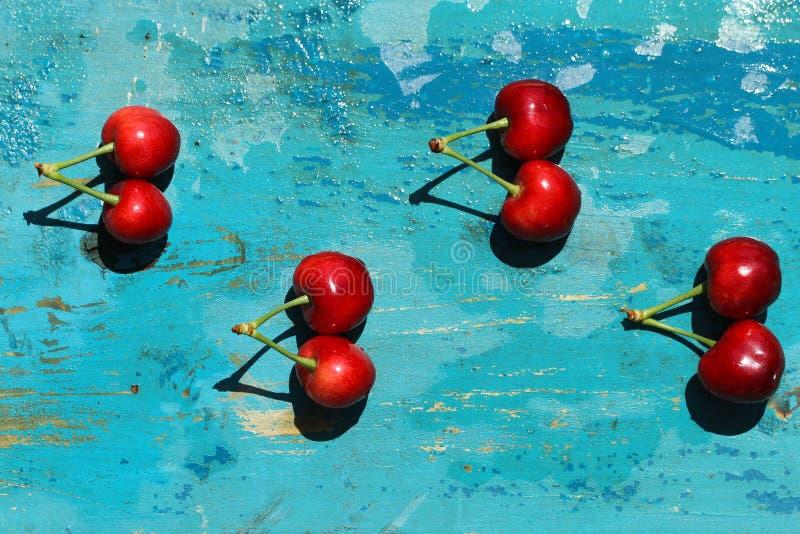 Świeże wiśnie na błękitnym drewnianym tle zdjęcia stock