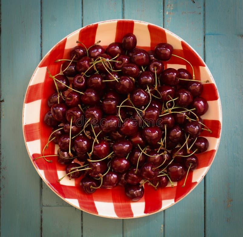 Świeże wiśnie w Czerwonym Gingham talerzu obrazy stock
