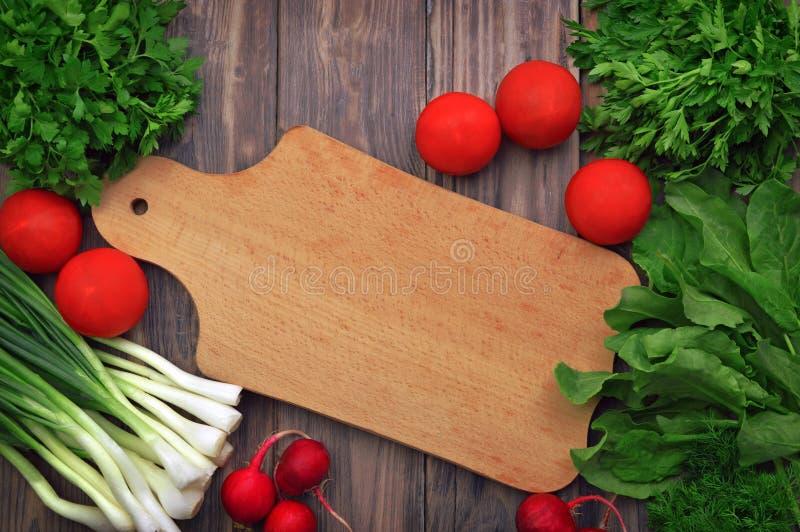 Świeże zielenie, warzywa i kulinarni naczynia na drewnianym tle, Mieszkanie nieatutowy witaminy Lato dieta Jarski lub zdrowy jedz zdjęcie royalty free