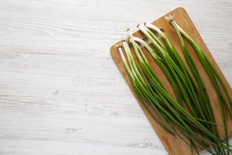 ?wie?e zielone cebule na bambusie wsiadaj? nad bia?ym drewnianym t?em, widok z g?ry Odg?rny widok, koszt sta?y, mieszkanie nieatu fotografia stock