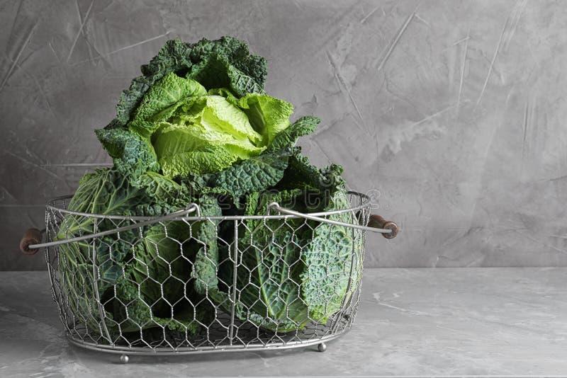 Świeże zielone kapusty pikantne w koszyku na stole na szarym tle Spacja dla tekstu obraz stock