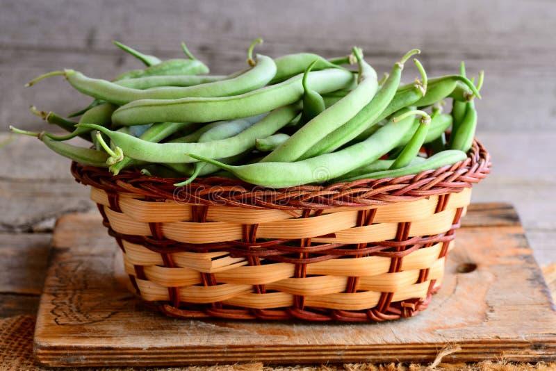 Świeże zielone smyczkowe fasole w łozinowym koszu drewnianej desce i Młode fasolki szparagowe, naturalny źródło żywienioniowy włó zdjęcia stock