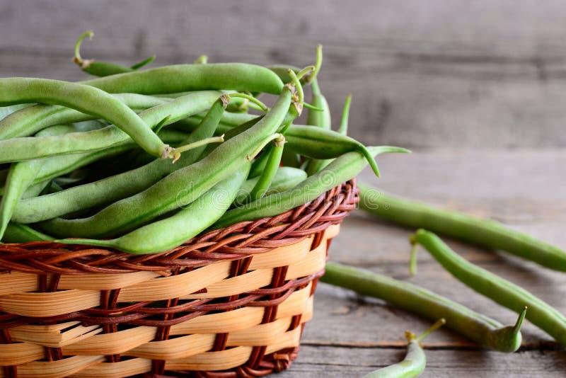 Świeże zielone smyczkowe fasole w łozinowym koszu Młode fasolki szparagowe, dobry źródło włókno, witaminy i kopaliny, Drewniany t zdjęcie stock