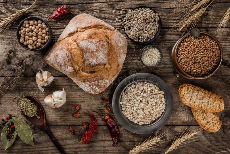 Świeżego chleba, pikantności i zboży wybór w pucharach na nieociosanym drewnianym tle, Zdrowy karmowy poj?cie, odg?rny widok, mie fotografia stock