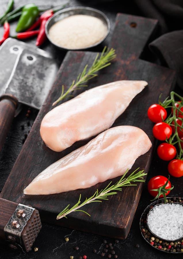 Świeżego Surowego Organicznie kurczaka Polędwicowa pierś na rocznik desce z mięsnymi siekierkami i pikantność z ziele na d obraz royalty free