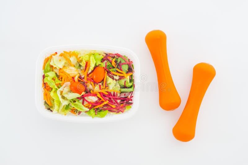 Świeżego warzywa sałatka w lunchu pudełku z pomarańczowymi dumbbells ćwiczy wyposażenie na bielu Aktywni zdrowi styl życia, dobre obraz royalty free