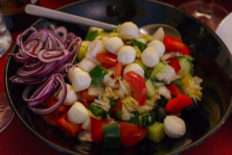 Świeżego warzywa sałatka z mozzarella piłkami dekorował z czerwonymi cebulkowymi pierścionkami zdjęcia stock