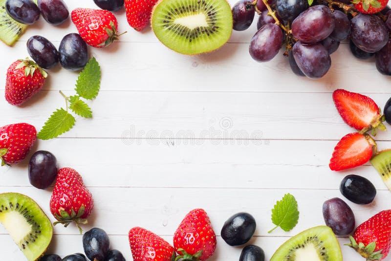 Świeżej owoc kiwi truskawkowi winogrona na bielu stole z kopii przestrzenią zdjęcia royalty free