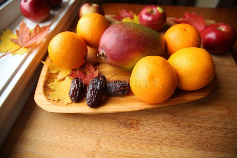 Świeżej owoc mango, jabłka, pomarańcze i daty w drewnianym talerzu, zdjęcia stock