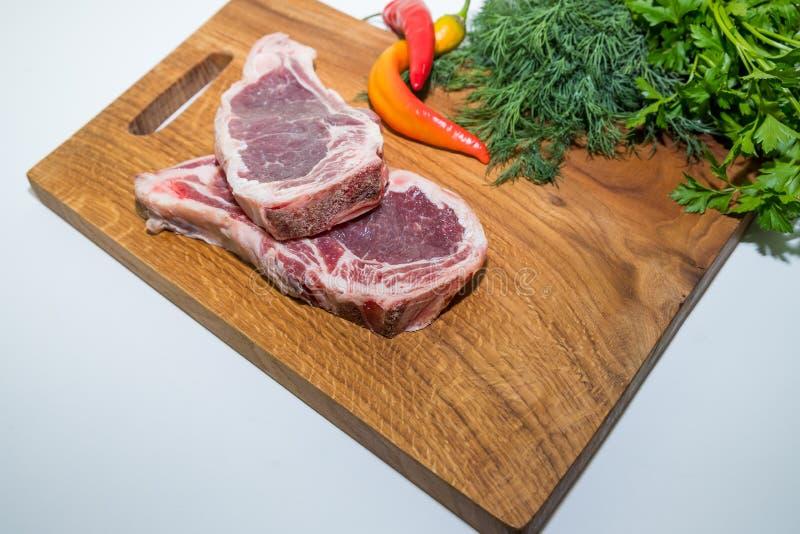 Świeżej surowej wołowiny mięsny stek, gorący pieprz i koper na drewnianej tnącej desce nad stołem Surowy mięso na drewnianej desc zdjęcie stock