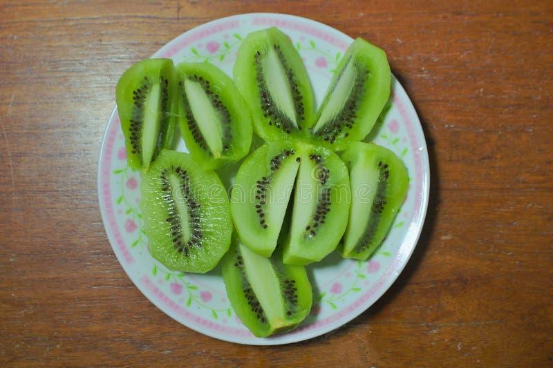Świeżo ciie kiwi owoc, łączącą w różnorodność naczyniach na drewnianym talerzu zdjęcie royalty free