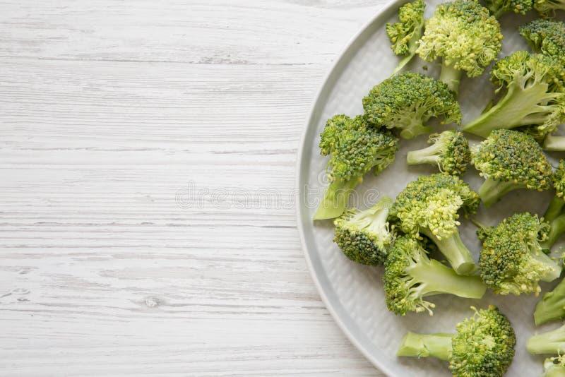 Świeżo ciie surowych brokuły na szarość talerzu nad białym drewnianym tłem, odgórny widok Mieszkanie nieatutowy, od above, koszt  obraz royalty free