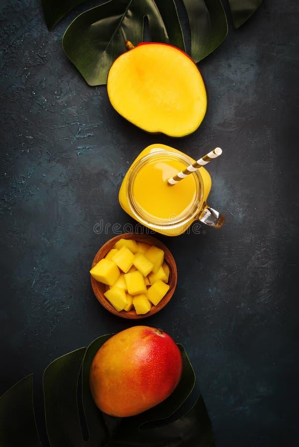 Świeżo gniosący świeży mangowy sok w wielkim szklanym słoju z świeżą owoc na zmroku - błękitny tło, miejsce dla teksta, odgórny w zdjęcia royalty free