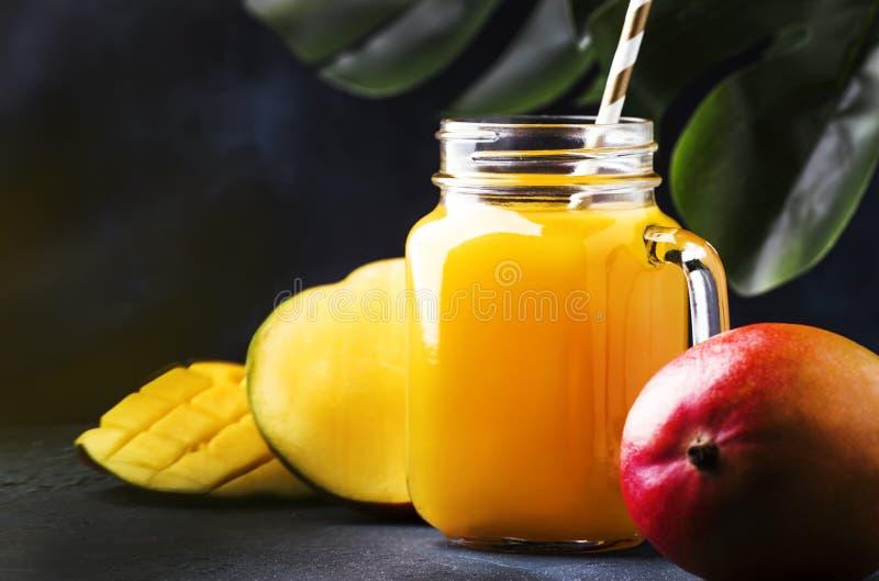 Świeżo gniosący świeży mangowy sok w wielkim szklanym słoju z świeżą owoc na zmroku - błękitny tropikalny tło, kopii przestrzeń,  obrazy stock