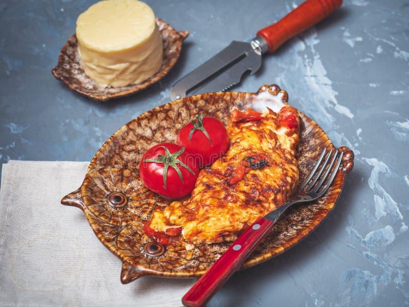 Świeżo gotujący omlet z warzywami i serem na dekoracyjnym talerzu z świeżymi czerwonymi pomidorami fotografia stock