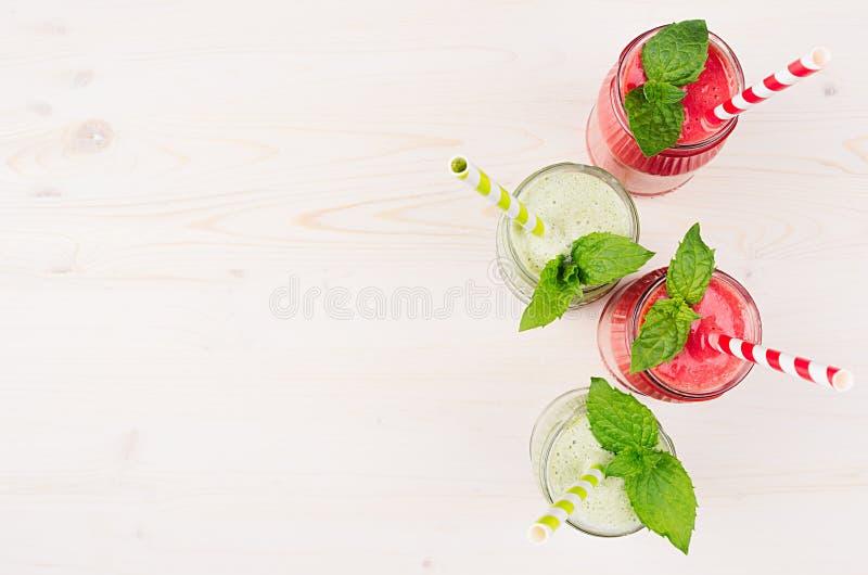 Świeżo mieszający zielony i czerwony owocowy smoothie w szkle zgrzyta z słomą, nowi liście, odgórny widok obrazy stock
