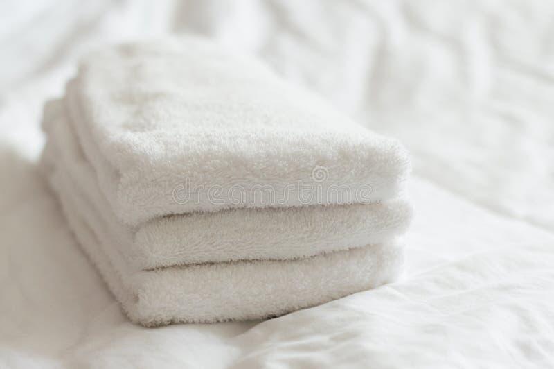 Świeżo myjący biali ręka ręczniki brogujący na białym łóżku obrazy royalty free