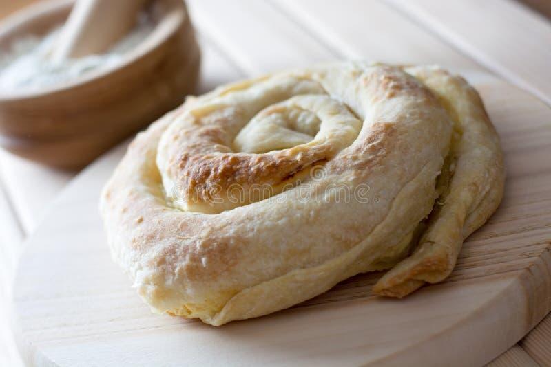 Świeżo piec ślimakowaty serowy kulebiak na drewnianym talerzu obraz stock