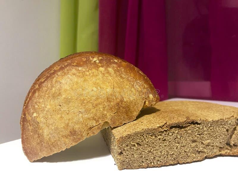 Świeżo piec bochenki chleb z rumianą skorupą kłamają na stole Widoczny plasterka bochenek fotografia stock