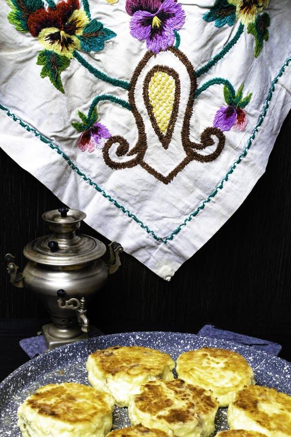 Świeżo piec chałupa sera bliny z rodzynkami na niecce z teapot Smażyć proces Odgórny widok obraz stock